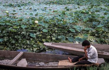 Srinagar  Indien  Mann sitzt in einem Holzboot auf dem Dal-See