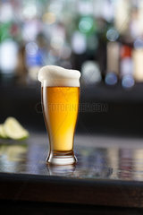 Glass of beer on wooden table and blurred background.