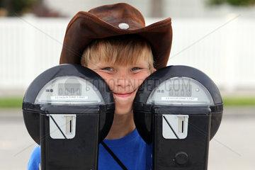 Saint Petersburg  USA  Junge mit Cowboyhut schaut hinter zwei Parkuhren hervor