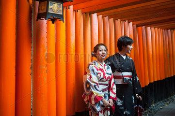 Kyoto  Japan  Zwei Japanerinnen stehen in einem Torii-Weg zum Fushimi Inari-Taisha