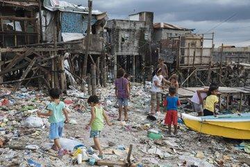 Kinder spielen im Plastikmuell am Ufer von Navotas