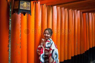 Kyoto  Japan  Eine Japanerin posiert in einem Torii-Weg zum Fushimi Inari-Taisha