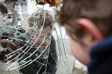 Berlin  Deutschland  ein Junge kniet auf einem zerbrochenen Spiegel