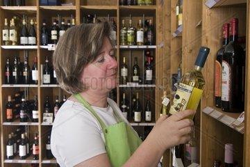 Einzelhandelsverkaeuferin prueft Wein