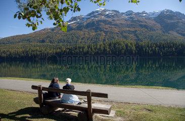 St. Moritz  Schweiz  Spaziergaenger bei einer Pause am St. Moritzersee