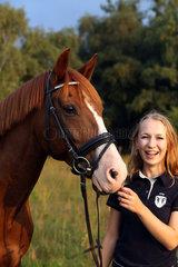Brieselang  Deutschland  lachendes Maedchen mit ihrem Pferd im Portrait