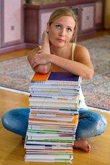 Eine Studentin sitzt vor einem Stapel Buecher beim lernen