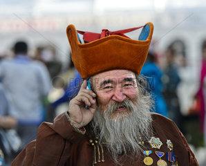 Aelterer Mann mit Bart  Kappe und Orden telefoniert mit einem Mobiltelefon  Ulanbator  Mongolei