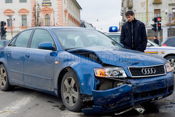 Oradea  Rumaenien  ein Mann steht neben einem Unfallauto