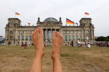 Berlin  Deutschland  Kinderfuesse recken sich vor dem Reichstagsgebaeude in die Luft