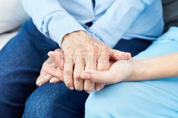 Altenpfleger haelt troestend Hand einer alten Frau