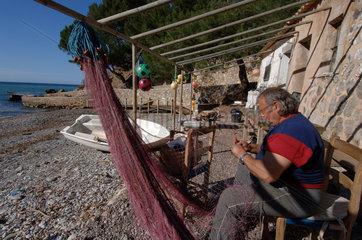 Escorca  Spanien  ein Fischer repariert sein Netz