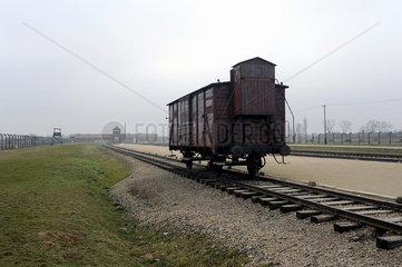 Auschwitz  Polen  Gueterwaggon vor dem Torhaus des Konzentrationslager Auschwitz-Birkenau