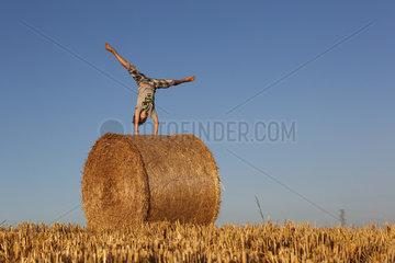 Torre Alfina  Italien  Junge turnt auf einem Strohballen herum
