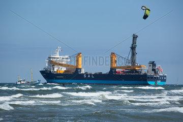 Rostock  Deutschland  Kitesurfer und Frachtschiff in der Ostsee