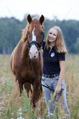 Brieselang  Deutschland  Maedchen und Pferd auf einer Sommerwiese im Portrait