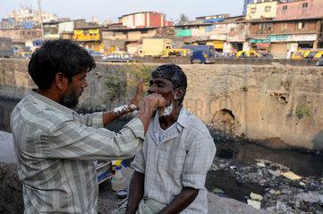 Mumbai  Indien  ein Strassenbarbier rasiert einen Kunden