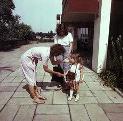Weimar  DDR  Erzieherin begruesst im Beisein der Mutter ein kleines Maedchen