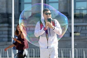 Berlin  Deutschland  Mann steht hinter einer grossen Seifenblase