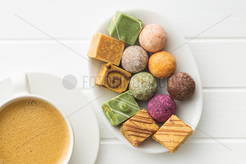 Various sweet candies and coffee cup.