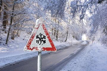 Warnschild vor Schneeglaette auf Landstrasse