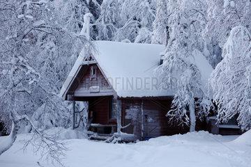 Aekaeskero  Finnland  eingeschneite Holzhuette