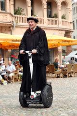 Wittenberg  Deutschland  Lutherdarsteller Bernhard Naumann mit einem Segway-Roller