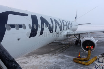 Kittilae  Finnland  Ramp Agent waermt im Winter das Triebwerk eines Flugzeugs vor dem Start