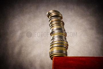 Gestapelte Muenzen an einer Tischkante