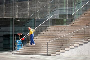 Berlin  Deutschland  Reinigungsktraft auf den Stufen des Marie-Elisabeth-Lueders-Haus
