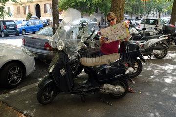 Orvieto  Italien  Frau lehnt an einem Motorroller und studiert einen Stadtplan