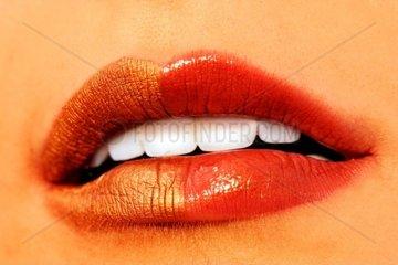 Makroaufnahme glaenzender Lippen mit goldenem und rotem Lippenstift