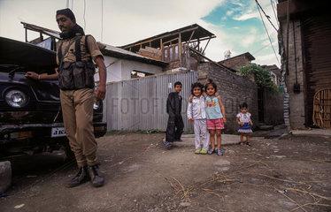 Srinagar  Indien  ein Soldat und spielende Kinder waehrend der Ausgangssperre