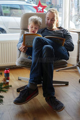 Utrecht  Niederlande  Vater schaut sich mit seinem Sohn ein Bilderbuch an
