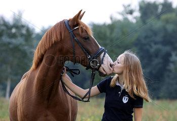 Brieselang  Deutschland  Maedchen kuesst ihr Pferd auf die Nuestern