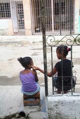 Havanna  Kuba  zwei Maedchen hoeren auf der Strasse zusammmen Musik mit einem iPod