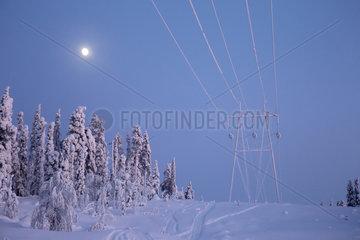 Aekaeskero  Finnland  vereiste Hochspannungsleitungen und Strommast bei Mondschein