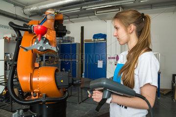 Posen  Polen  Studentin demonstriert die Arbeit mit einem Industrieroboter