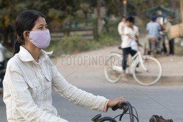 Fahrradfahrerin mit Gesichtsmaske / Siem Reap / Kambodscha / SUEDOSTASIEN-R