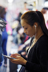 Hong Kong  China  Frau hoert Musik mit ihrem Smartphone