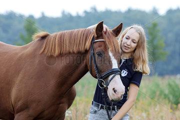 Brieselang  Deutschland  Maedchen schmust mit ihrem Pferd
