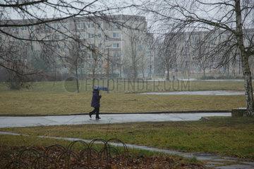 Brandenburg  Deutschland  eine Frau geht im stroemenden Regen durch einen Park
