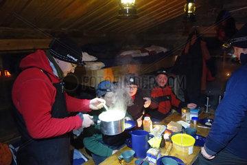 Aekaeskero  Finnland  Menschen essen ihr Abendbrot in einer kalten Holzhuette