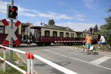 Kuehlungsborn  Deutschland  Fahrradfahrer warten an einer Eisenbahnschranke auf die Durchfahrt des Molli