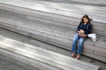 New York City  USA  eine Frau ruht sich aus auf den Baenken von The Highline