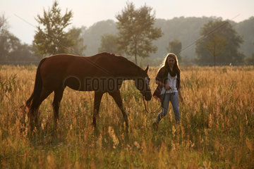 Brieselang  Deutschland  Maedchen geht mit ihrem Pferd am Abend auf einer Wiese spazieren