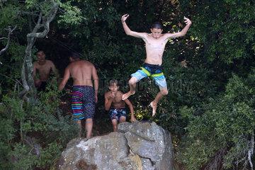 Bolsena  Italien  Junge springt mutig von einem hohen Felsen in den Bolsenasee