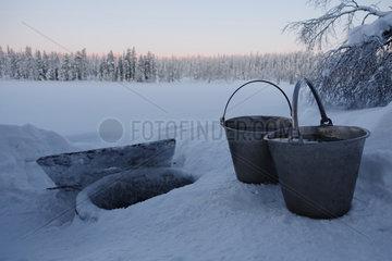 Aekaeskero  Finnland  Eimer mit frischem Wasser stehen im Schnee