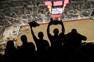 Spectators watching rodeo in stadium