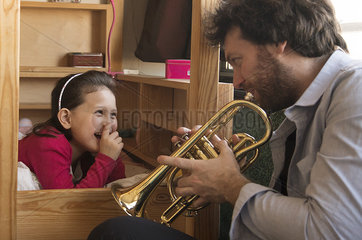 Father playing trumpet for little girl lying in bed